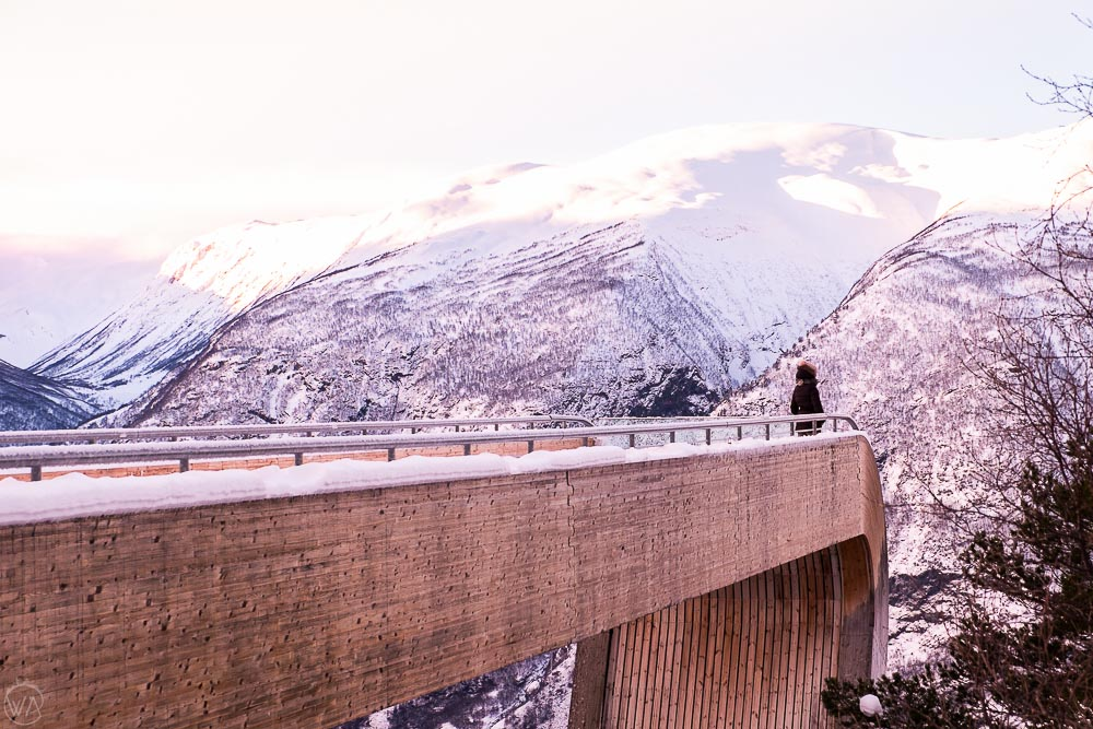Girl standing at the end of the viewing platform in Norway wearing Norway winter jacket and boots