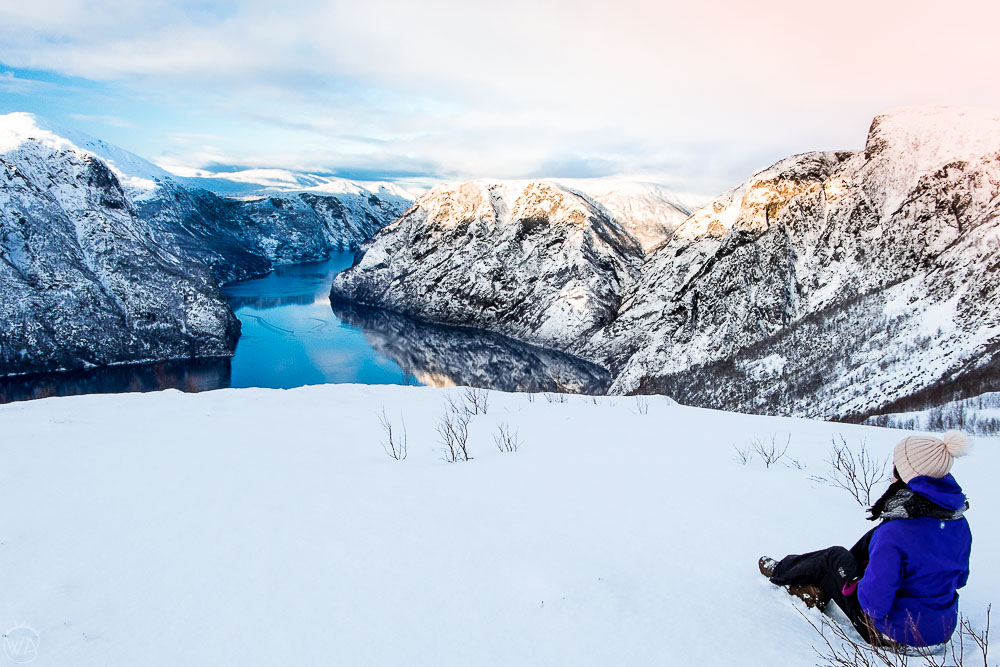 Girl wearing Norwegian winter jacket and hat in front of Norwegian fjords in winter