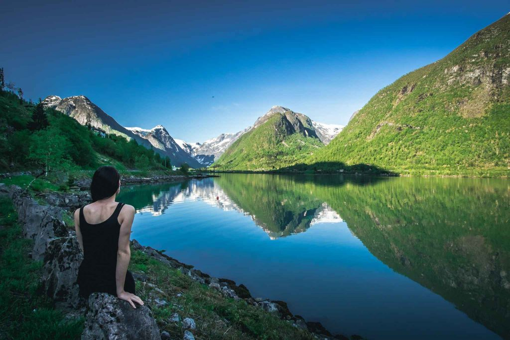 Girl sitting and watching fjords in Norway