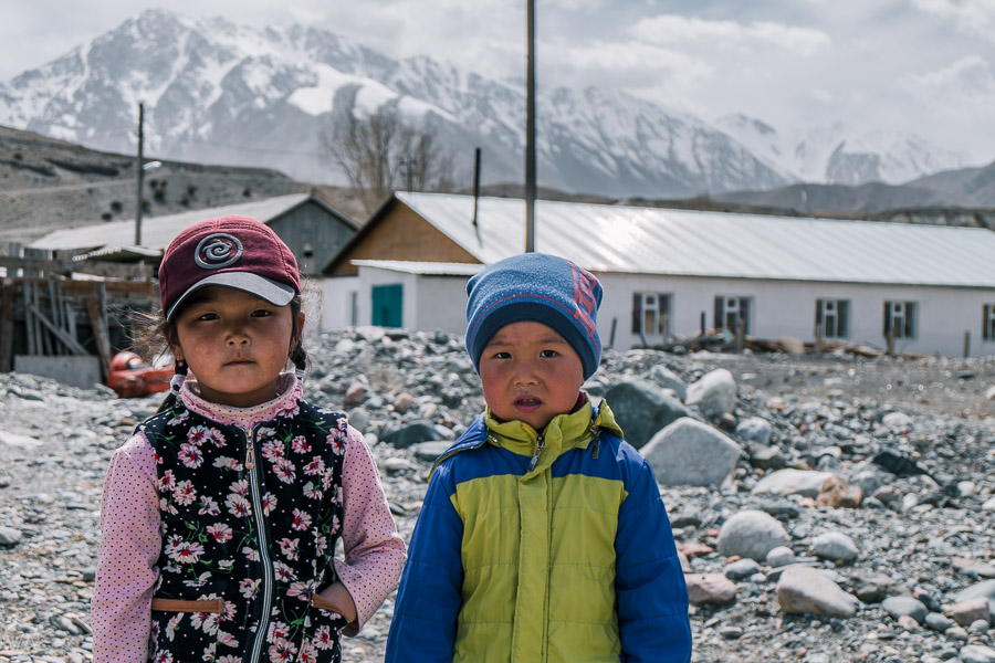 Local kids are curious of visitors, ghost town Engilchek, Sary Jaz valley, Kyrgyzstan