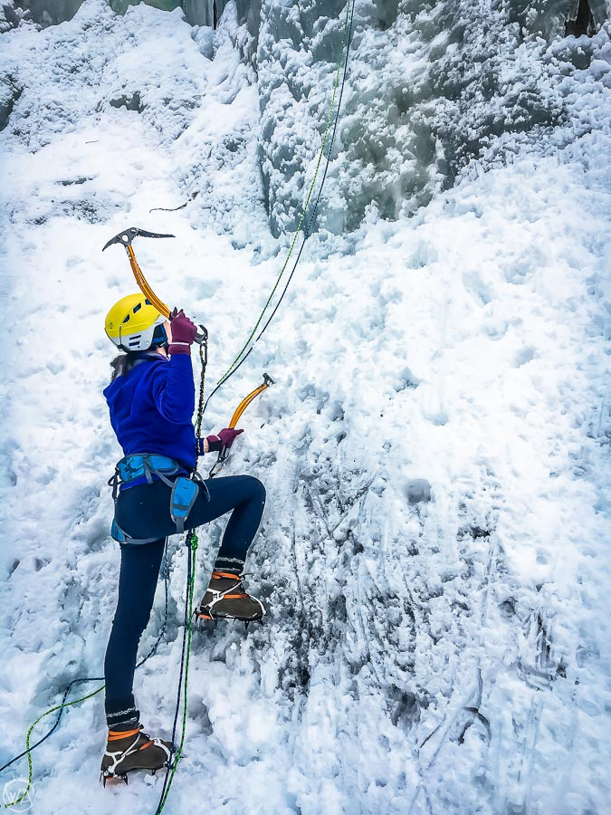 Girl wearing norwegian winter boots, crampons and climbing frozen waterfall in Norway