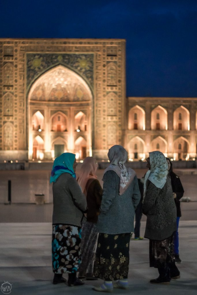 Locals in front of Registan at night, Samarkand, Uzbekistan