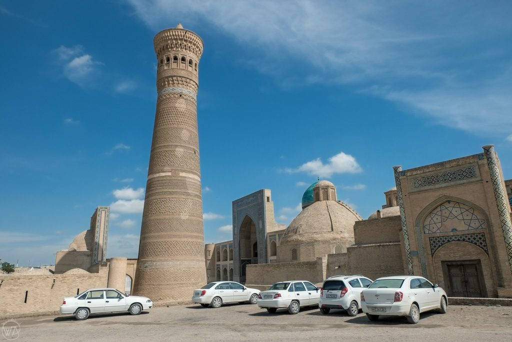 White cars in front of Kalon Minaret, Bukhara, Uzbekistan