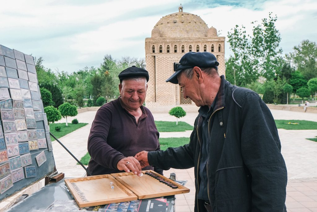Locals playing in the Samonids Recreation Park, with the Mavzoley Samanidov in the background